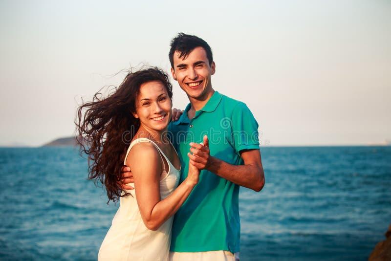 muchacha e individuo que abrazan contra el mar azul fotos de archivo