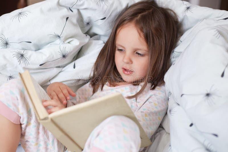 Muchacha educada leyendo su cuento de hadas favorito, niño sentado en cama con libro, niño preparándose para ir a la cama, pasa fotos de archivo