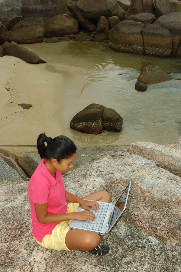 Muchacha el vacaciones usando el ordenador portátil afuera foto de archivo