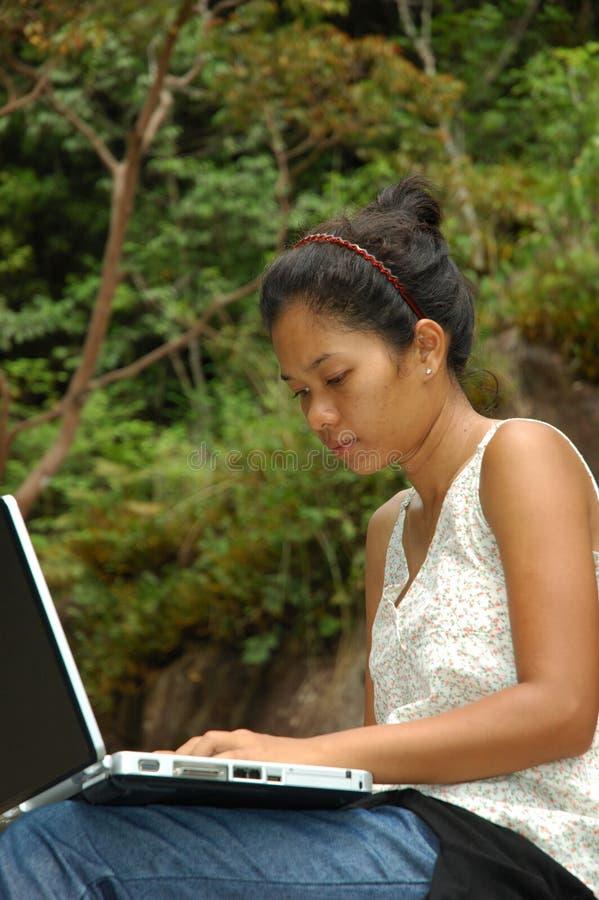 Muchacha el vacaciones usando el ordenador portátil afuera imagen de archivo libre de regalías