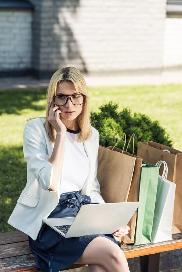 muchacha elegante atractiva que habla por smartphone y que usa el ordenador portátil mientras que se sienta en banco foto de archivo libre de regalías