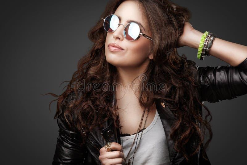 Muchacha elegante bastante joven en la chaqueta de cuero y gafas de sol redondas fotografía de archivo libre de regalías