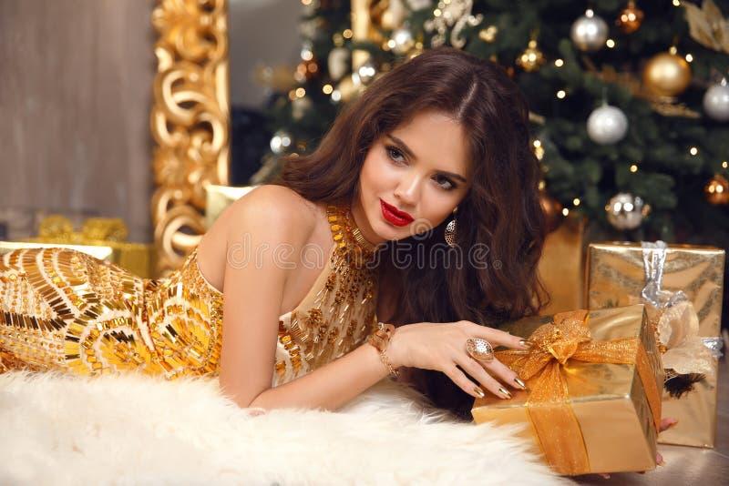 Muchacha elegante de la Navidad que miente en vestido de oro con la joyería costosa fijada en partido sobre las cajas de regalo E fotografía de archivo libre de regalías