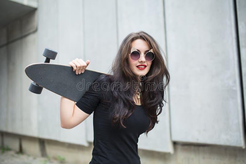 Muchacha elegante del adolescente con un longboard imagen de archivo