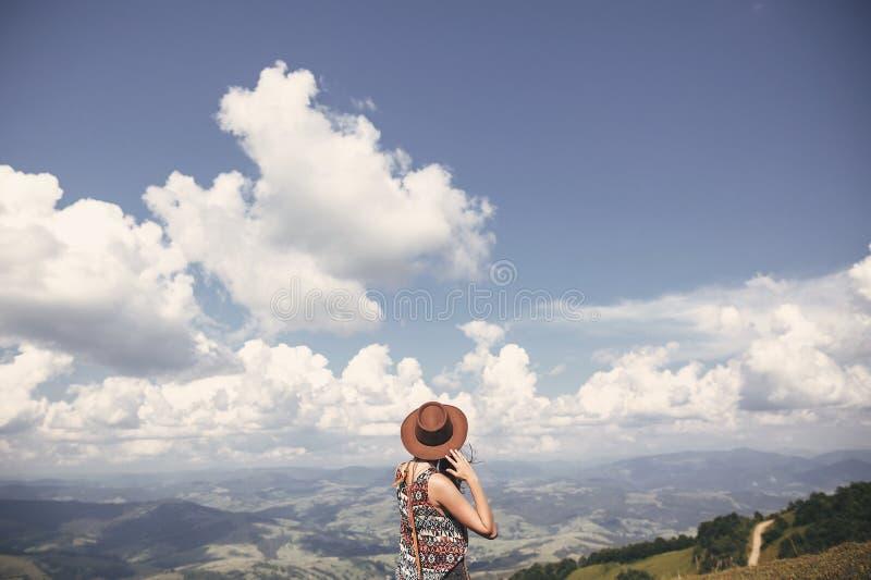 Muchacha elegante del inconformista en sombrero que camina encima de las montañas soleadas Mujer joven feliz que explora en monta foto de archivo