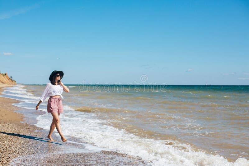 Muchacha elegante del inconformista en sombrero que camina en la playa y la sonrisa Vacaciones de verano La mujer joven feliz del imagen de archivo