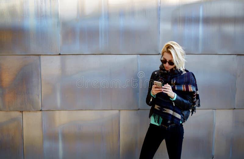 Muchacha elegante del inconformista que charla en el teléfono de célula mientras que se opone a fondo metálico urbano fotografía de archivo