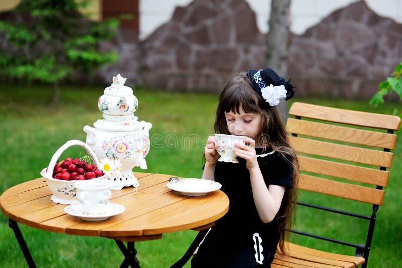Muchacha elegante del niño que tiene una fiesta del té al aire libre foto de archivo