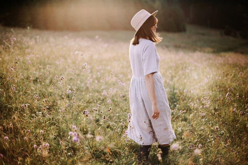 Muchacha elegante en el vestido de lino que camina entre wildflowers en prado soleado en montañas Mujer de Boho que se relaja en  imágenes de archivo libres de regalías