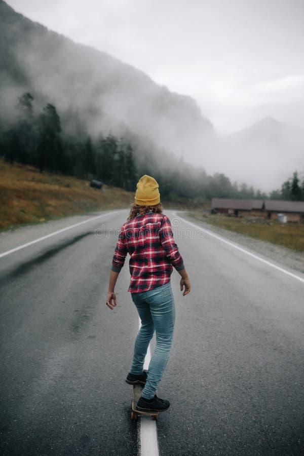 Muchacha elegante en un casquillo en un topetón en la carretera en las montañas con un longboard imágenes de archivo libres de regalías