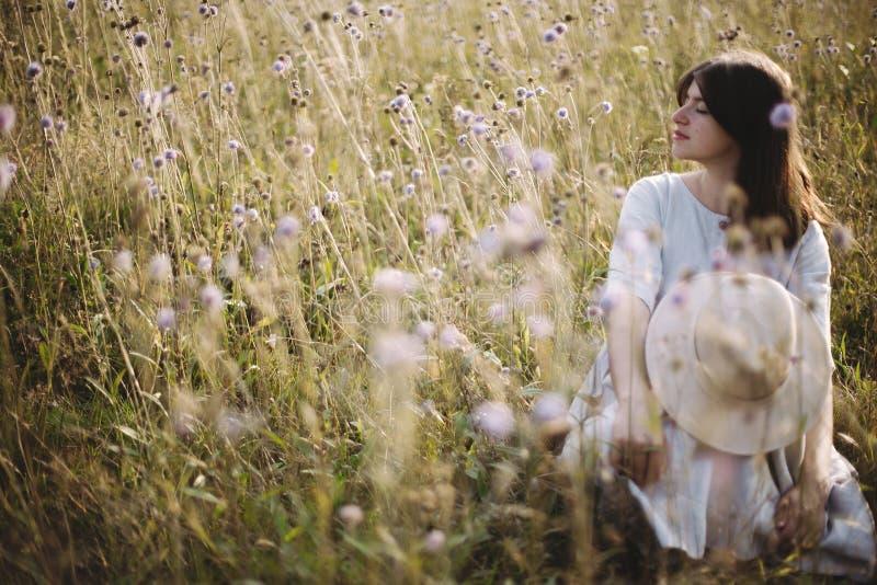 Muchacha elegante en vestido rústico y el sombrero que se sientan entre wildflowers e hierbas en prado soleado en montañas Mujer  foto de archivo libre de regalías