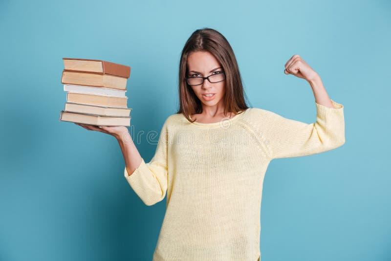 Muchacha elegante fuerte que sostiene los libros en lentes que llevan de una mano fotografía de archivo