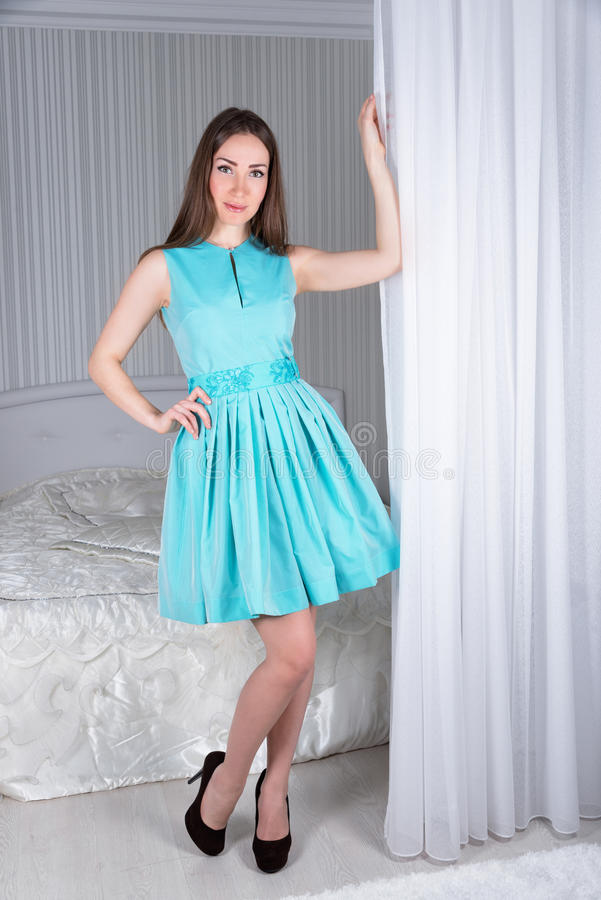 Muchacha elegante hermosa con el pelo largo en la presentación interior de lujo en vestido de noche imponente imagen de archivo libre de regalías