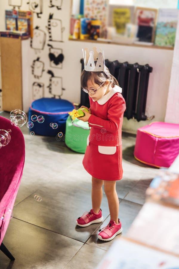 Muchacha elegante hermosa con Síndrome de Down que juega con las burbujas de jabón imagen de archivo libre de regalías