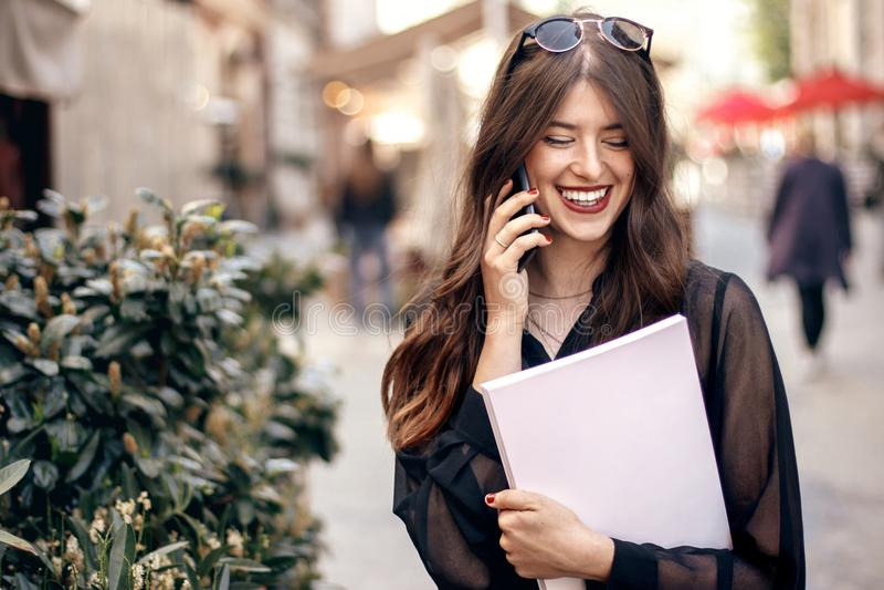 Muchacha elegante hermosa del inconformista que habla en el teléfono y que sostiene maga fotos de archivo libres de regalías