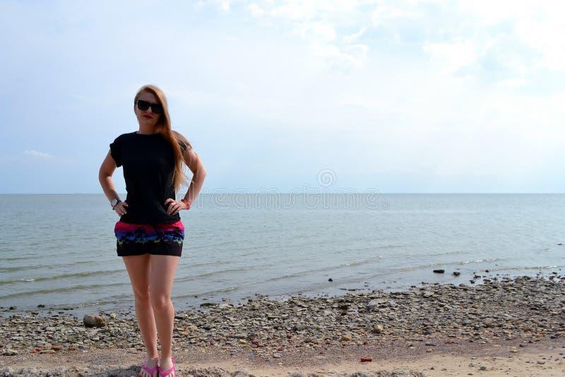 Muchacha elegante hermosa joven en una camiseta negra simple que presenta cerca del mar fotografía de archivo libre de regalías