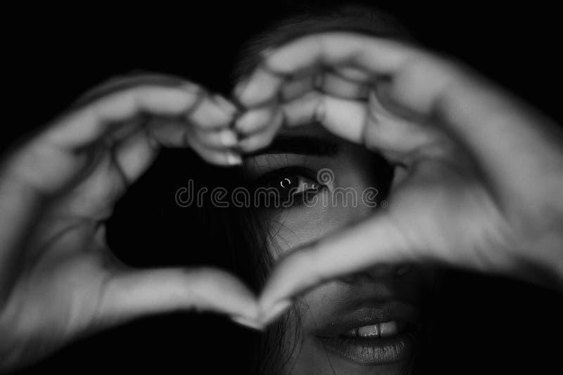Muchacha elegante hermosa que lleva a cabo las manos delante de la cara en forma de corazón Labios divididos levemente Ojos hermo imagen de archivo libre de regalías