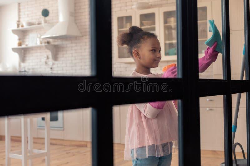 Muchacha elegante hermosa que lleva la blusa rosada que limpia la puerta de cristal imagen de archivo libre de regalías