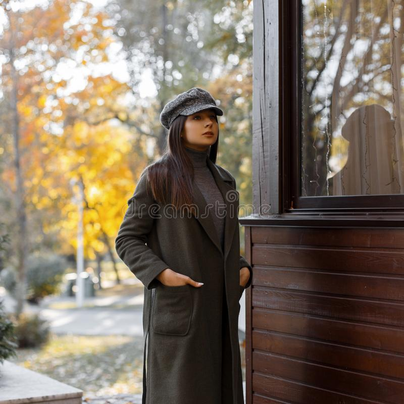 Muchacha elegante hermosa y joven en una capa gris del vintage y soportes de moda del casquillo durante el día en el parque del o foto de archivo