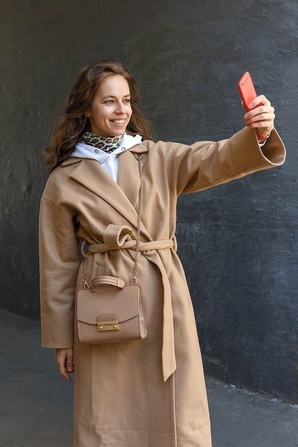 Muchacha elegante joven hermosa sonriente que sostiene su teléfono móvil en una mano y la fabricación de una foto del selfie fotos de archivo libres de regalías