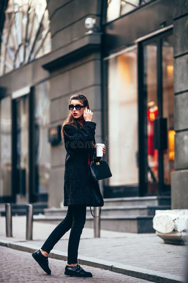 Muchacha elegante joven, pasando por Windows Vidrios de moda que llevan y una capa negra Guarda el café fotos de archivo libres de regalías