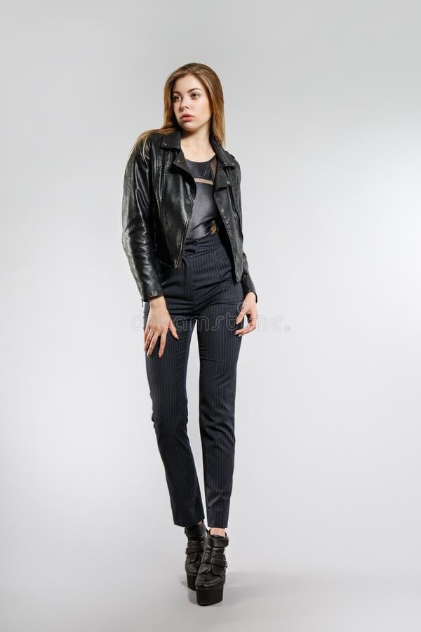 Muchacha elegante joven que presenta en el estudio Pantalones flacos negros, chaqueta de cuero negra foto de archivo libre de regalías