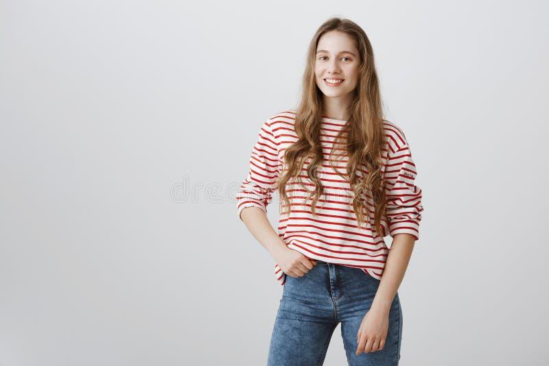 Muchacha elegante lista para ir a hacer compras Tiro interior del adolescente de pelo rubio emotivo en el suéter rayado que lleva imagen de archivo libre de regalías