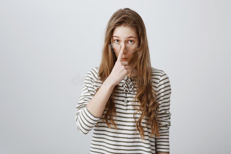 Muchacha elegante lista para utilizar su conocimiento Retrato de la mujer joven lista hermosa que fija los vidrios en nariz, mira fotografía de archivo