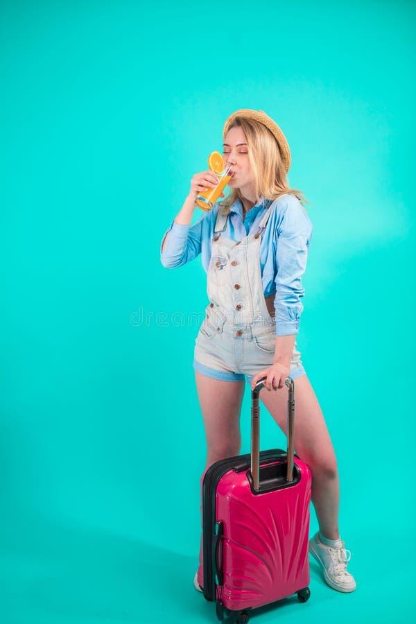 Muchacha elegante que bebe el zumo de naranja mientras que se coloca con la maleta foto de archivo libre de regalías