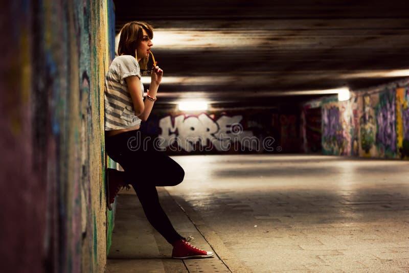 Muchacha elegante que se coloca en el túnel de la pintada del grunge, ciudad de chabola imagenes de archivo