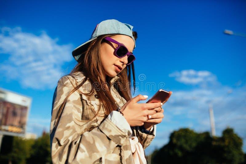Muchacha elegante que usa un smartphone, al aire libre fotografía de archivo