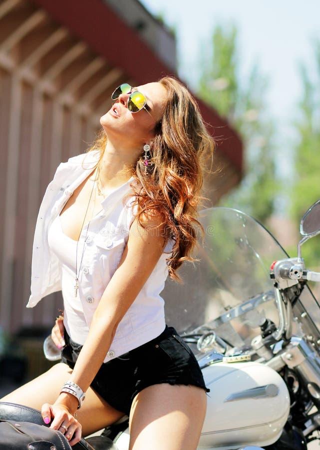 Muchacha elegante sobre los vidrios coloreados en una motocicleta imagen de archivo libre de regalías