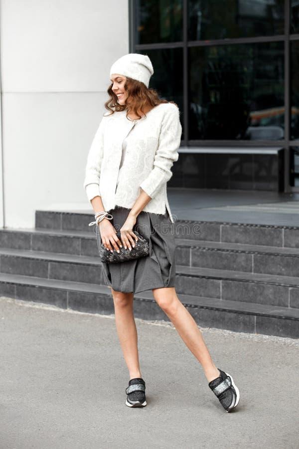 Muchacha elegante vestida en la falda gris de moda, la blusa blanca, el sombrero blanco y las actitudes de las zapatillas de depo fotos de archivo