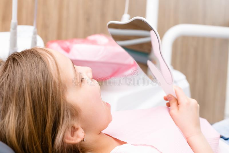Muchacha elemental de la edad que mira sus dientes en el espejo en clínica dental pediátrica foto de archivo