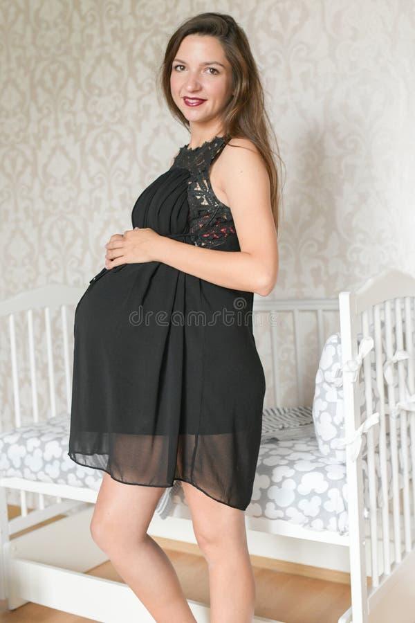 Muchacha embarazada cerca de la cama para un niño color blanco del kravatka para el niño preparación para el nacimiento de un niñ imagen de archivo libre de regalías