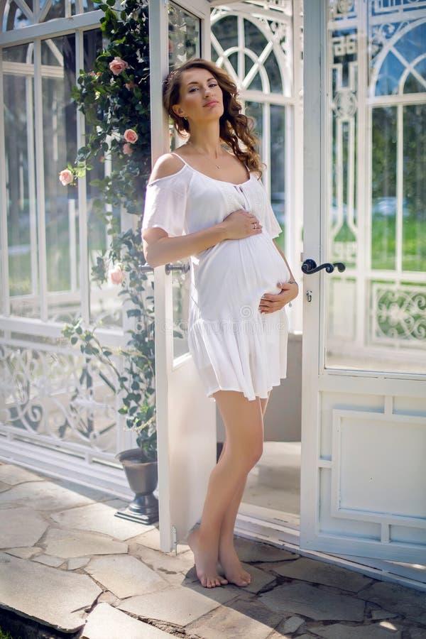 Muchacha embarazada en un vestido blanco en la calle foto de archivo libre de regalías