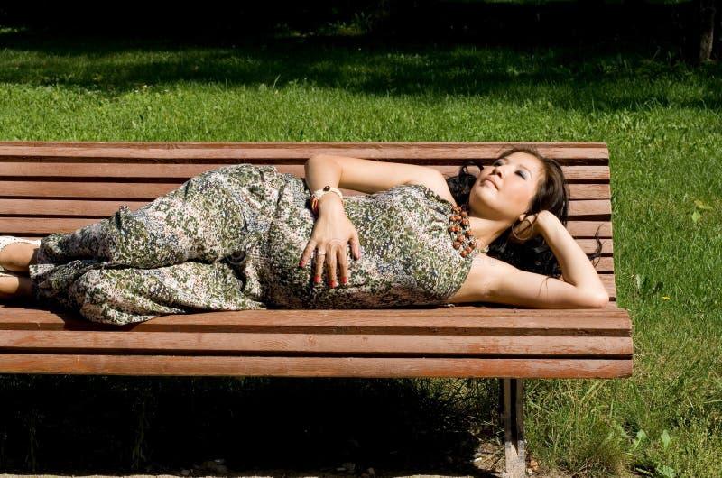 Muchacha embarazada hermosa que miente en banco fotografía de archivo libre de regalías