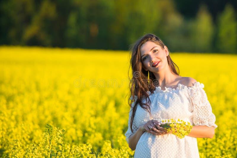 Muchacha embarazada que sostiene las flores Vientre de una mujer embarazada El concepto de embarazo Sobre la naturaleza verde fon fotos de archivo libres de regalías
