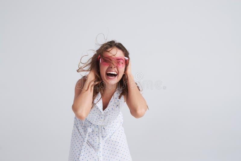 Muchacha emocionada en las gafas de sol rosadas que van locas foto de archivo
