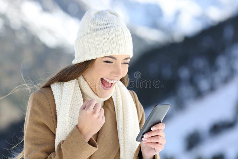Muchacha emocionada que comprueba noticias en línea en invierno imágenes de archivo libres de regalías