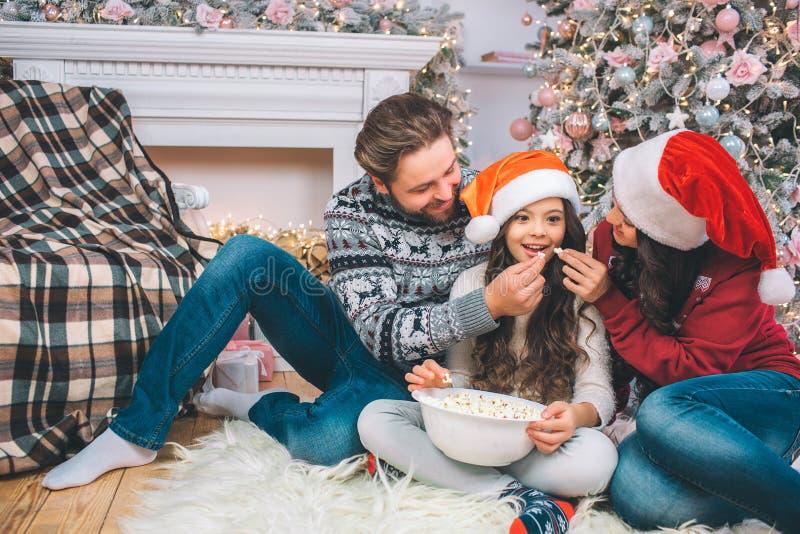 Muchacha emocionada que se sienta entre los padres y las miradas en dos pedazos de palomitas le dan El hombre joven y la mujer mi imagen de archivo