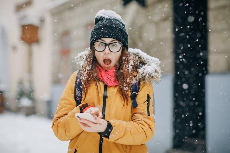 Muchacha emocionada que tiene una conversación telefónica móvil positiva en la calle fotos de archivo