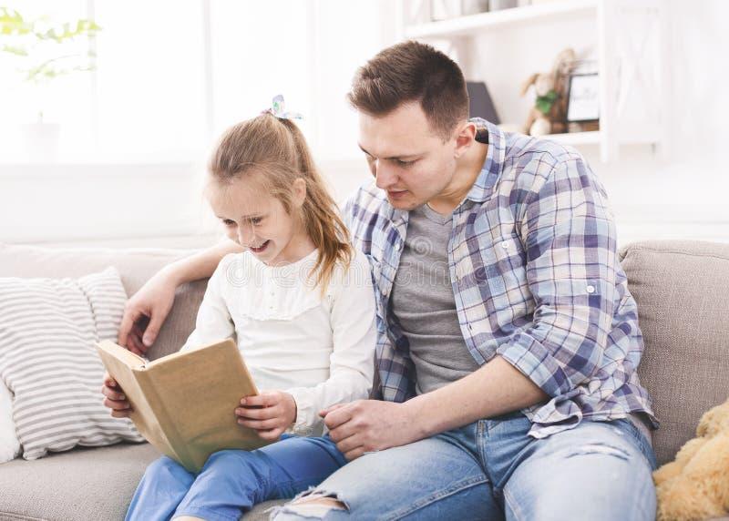 Muchacha emocionada y su padre que gozan del libro junto fotografía de archivo