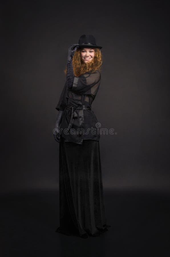 Muchacha emocional, pelirroja en una falda negra, blusa negra, sombrero negro y guantes negros imágenes de archivo libres de regalías