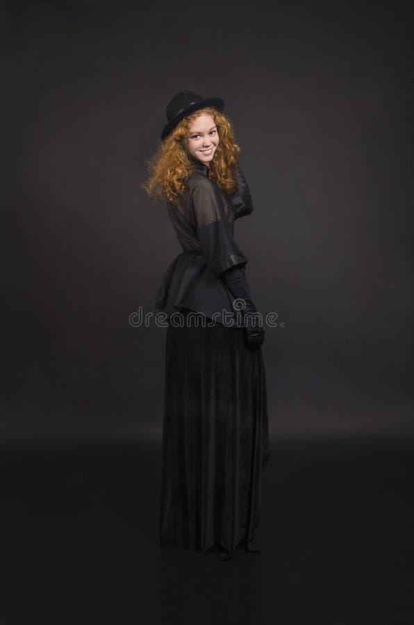 Muchacha emocional, pelirroja en una falda negra, blusa negra, sombrero negro y guantes negros fotografía de archivo libre de regalías