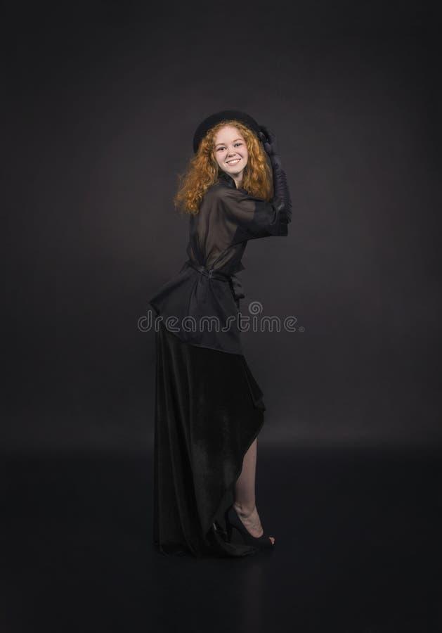 Muchacha emocional, pelirroja en una falda negra, blusa negra, sombrero negro y guantes negros imagen de archivo libre de regalías