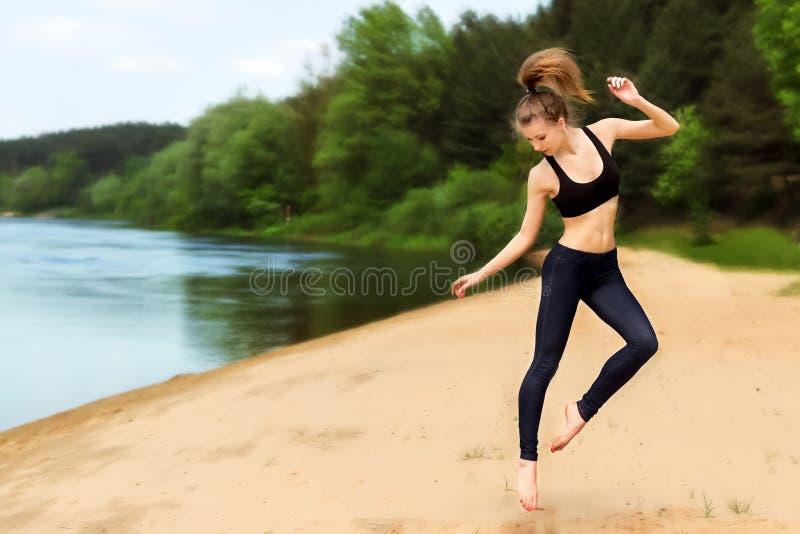 Muchacha enérgica joven que se contrata a aptitud en la playa cerca del río imagenes de archivo