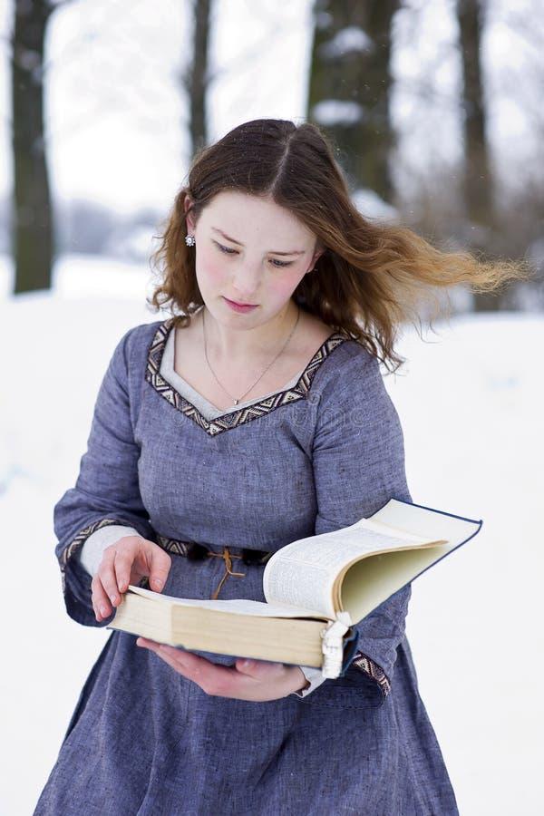 Muchacha en alineada medieval que lee el libro foto de archivo libre de regalías