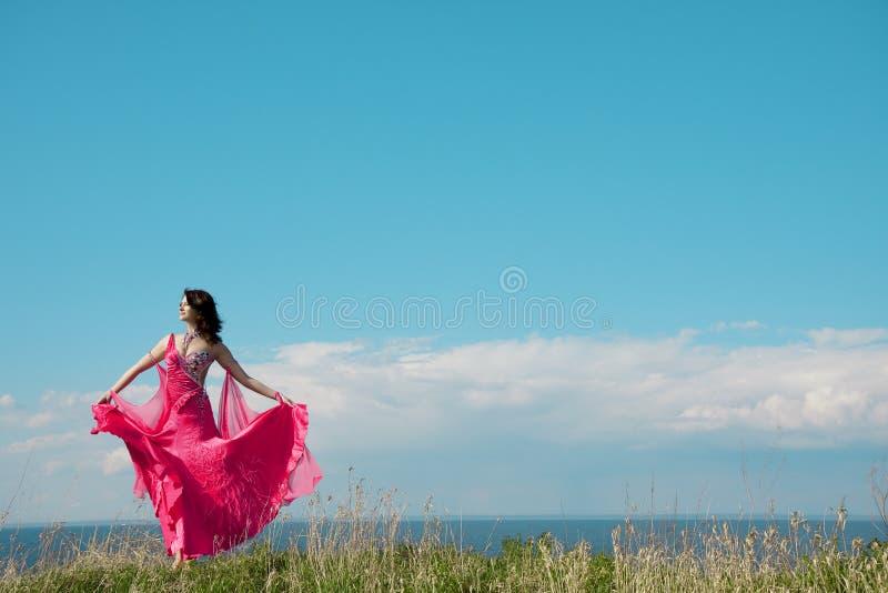 Muchacha en alineada rosada contra el contexto del cielo. imagen de archivo