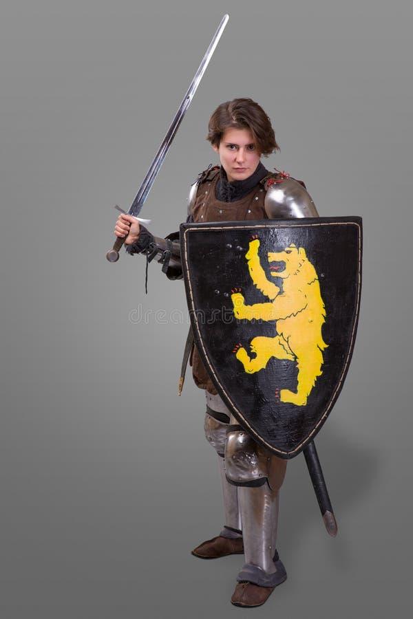 Muchacha en armadura con un escudo del wuth del caballero de la espada sobre fondo gris imagen de archivo